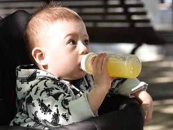 baby with orange juice bottle