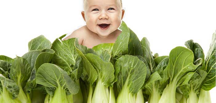 baby behind green veg